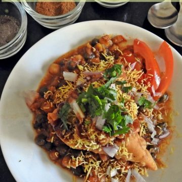Samosa Chaat is mashed samosa topped with peas or chole masala and topped with tangy chutneys, sev, onion and tomatoes if you wish.