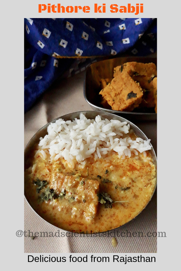 Rice and Pithore ki kadhi in a small bowl. A serving of pithore can also been seen.