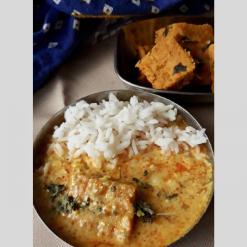a small plate of white steamed rice and Pithore ki Sabzi